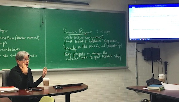 Janna teaching a class.  She is seated at the front of the class with notes about how to write a progress report on the board