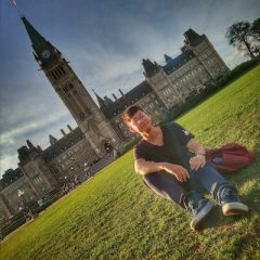 Xiaoran seated on the grass in front of Canadian Parliament building.