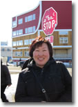 Maria in front of a stop sign written in English and Inuktitut