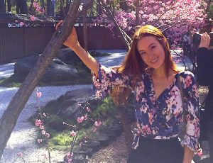 Taelor in front of trees filled with pink cherry blossoms