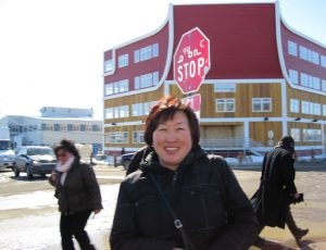 Maria in front of a stop sign written in Inuktitut