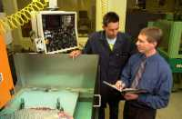 STC staff discussing machinery - about us