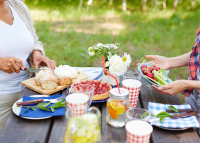 Reusable dishware with food and drinks on a picnic table.