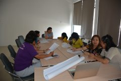 A group of participants sit around a table with paper and supplies to think of ideas