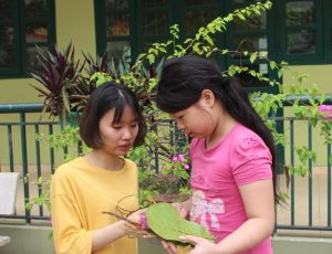 A woman stands outside next to a tree with a girl. They are looking at a book