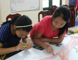 Two girls sitting at a table leaning over a poster working on it.