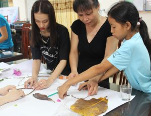 Two girls and a woman work on a project together. They are putting material on paper