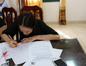 A girl sitting at a table writing on a paper