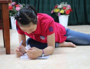 A girl sitting on the floor leaning over looking at a book