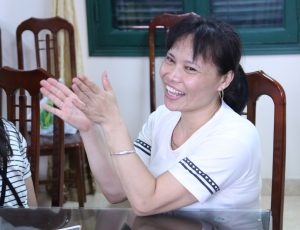 A woman sitting down smiling and clapping