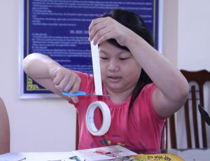 A girl working on a craft cutting a paper