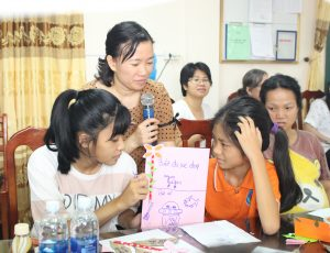 A group of girls looking at a paper with a drawing on it. A woman stands amidst them holding a microphone