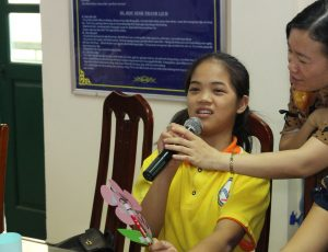 A girl seated on a chair speaking into a microphone. The person holding the microphone is not in the photo.