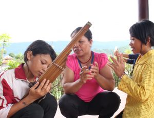 Three women seated together looking at a wooden instrument that one of them is holding