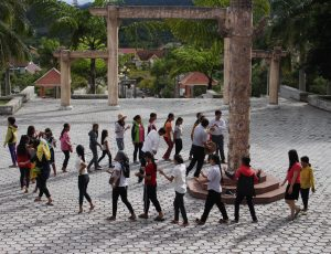 a group of women and girls walking in a line in a courtyard