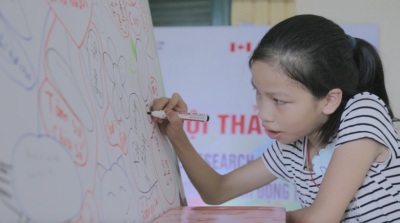 a girl drawing on a paper