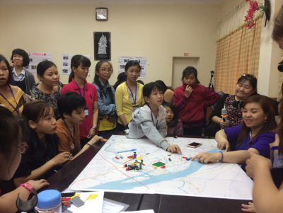 A group of girls and women are surrounding a table with a map on it. One woman and one girl are pointing at something on the map