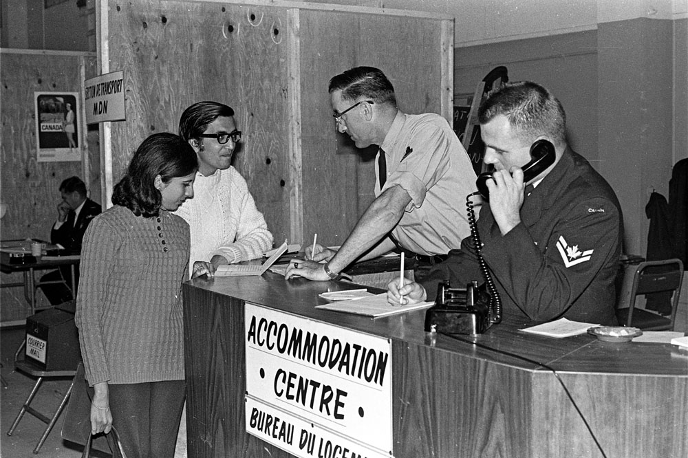 Mr. and Mrs. Anil Lalani receive accommodation instructions while Cpl. Robert Boudreau makes arrangements on the phone. (Caption - Seven Crested Cranes)