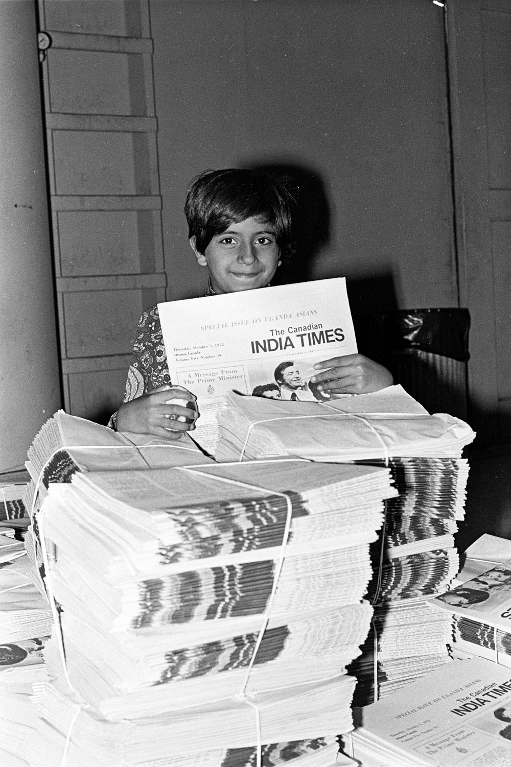 "Child holds stack of newspaper the ""Canadian Indian Times"""